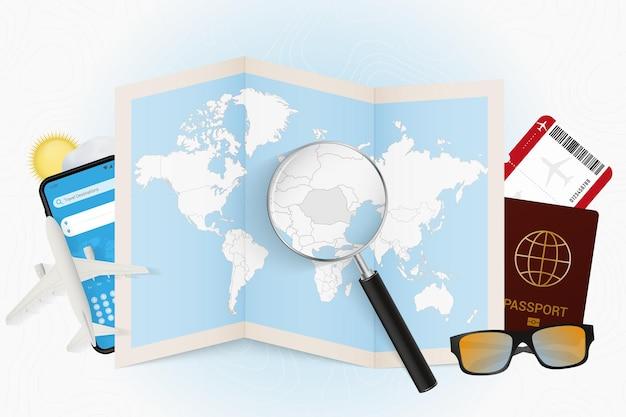 Reisbestemming roemenië, toerismemodel met reisuitrusting en wereldkaart met vergrootglas op roemenië.