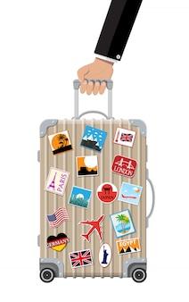 Reistas in de hand. plastic koffer met stickers.