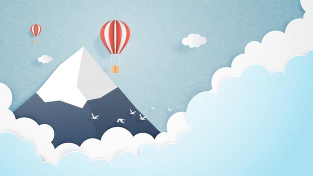 Reizen concept. origami maakte hete luchtballon die over berg met wolken en hemelachtergrond en ruimte vliegt.