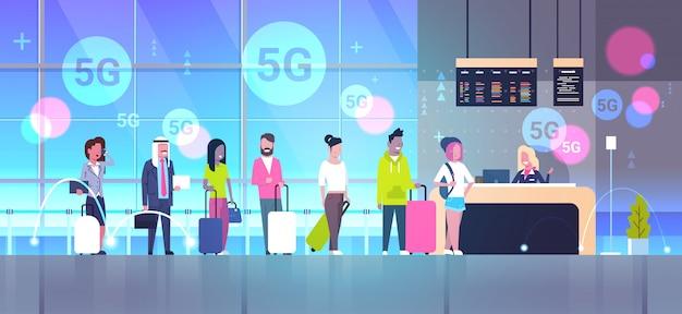 Reizigers met koffers staan in de rij in de rij bij de registratiebalie 5g online draadloos systeem verbinding mix race mannen vrouwen passagiers in luchthaventerminal horizontaal volledige lengte
