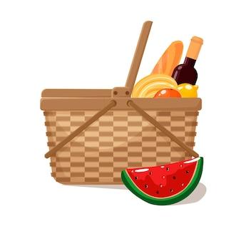 Rieten picknickmand vol boodschappen een fles wijn een stokbrood bananen sinaasappels watermeloen