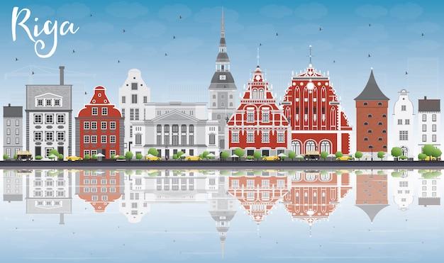 Riga skyline met bezienswaardigheden, blauwe hemel en reflecties.
