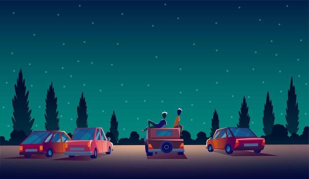 Rijd in het theater met auto's die 's nachts in de openluchtparking staan