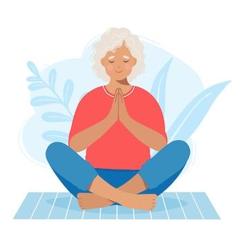 Rijpe hogere vrouw die zen-positie op yogamat beoefent