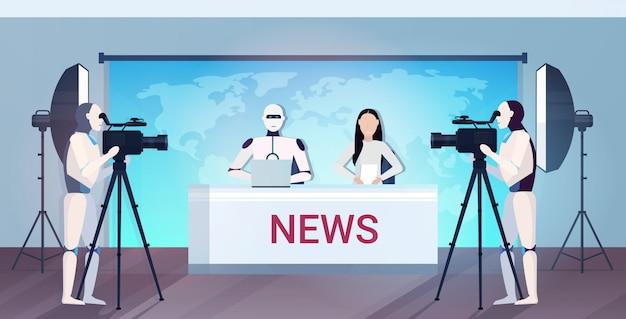 Robotachtige cameramannen opname robot en vrouw tv-presentatoren zitten aan tafel in nieuwsstudio