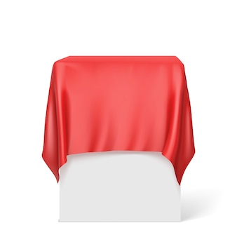 Rode doek op een vierkant voetstuk dat op wit wordt geïsoleerd.