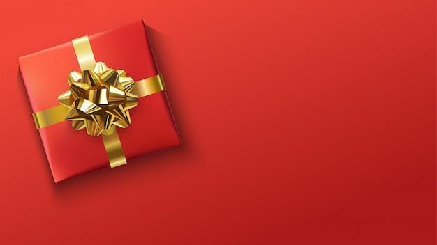Rode geschenkendoos met gouden strik op rood