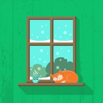 Rode kat slaapt en een kop warme koffie of thee staat op de vensterbank