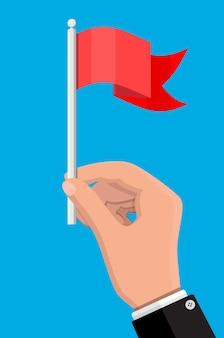 Rode vlag op metalen vlaggenmast in de hand