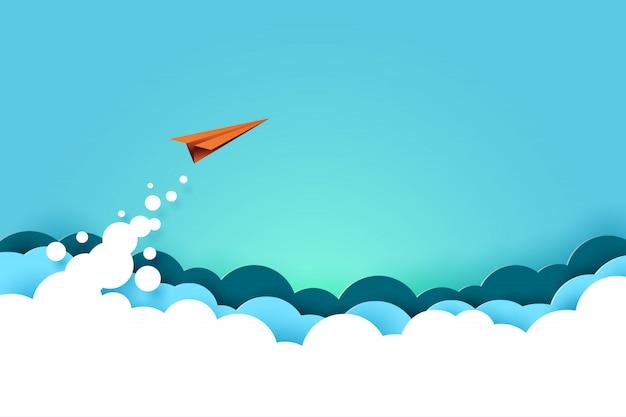 Rood papieren vliegtuigje vliegen van wolken op blauwe hemelachtergrond.