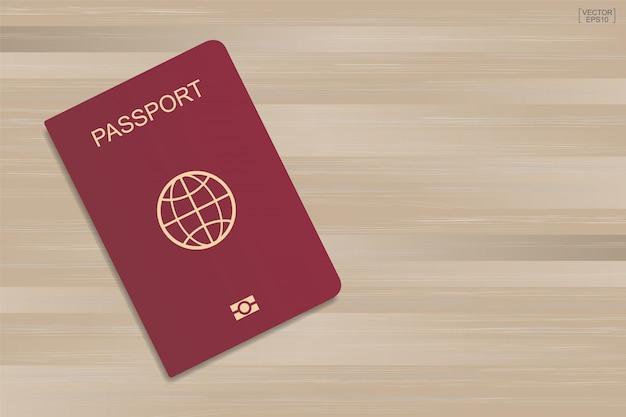 Rood paspoort op houten patroon en textuurachtergrond.