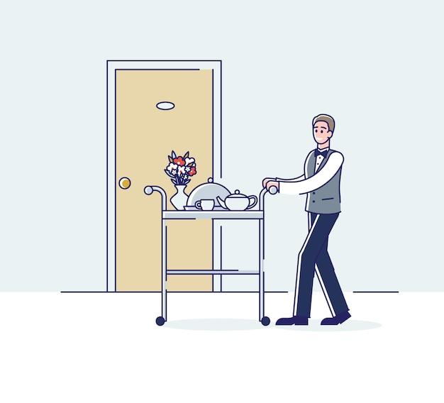 Roomservice medewerker draagt trolley met diner of ontbijt naar de bezoekerskamer.