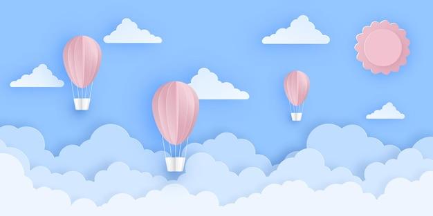 Roze mooie heteluchtballonnen die over pluizige wolken in de lucht vliegen met zon