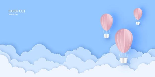 Roze mooie heteluchtballonnen die over wolken in de lucht vliegen papier gesneden stijl