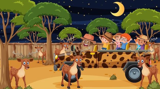 Safari bij nachtscène met veel kinderen die naar een hertengroep kijken