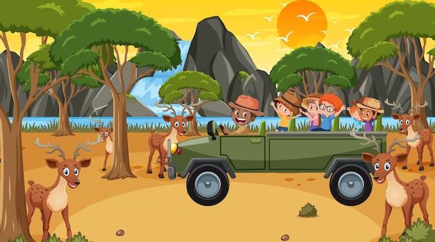 Safari bij zonsondergangtijdscène met kinderen die naar hertengroep kijken