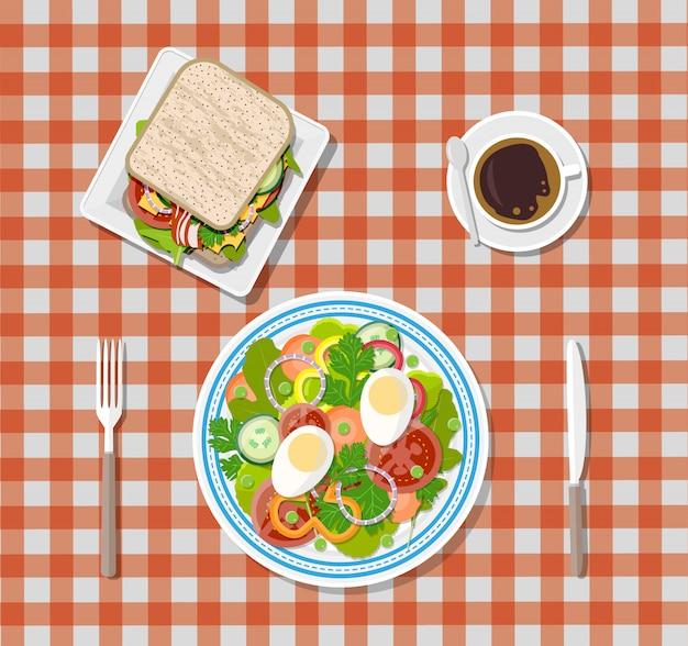 Salade, koffie, sandwich. borden, vork, mes