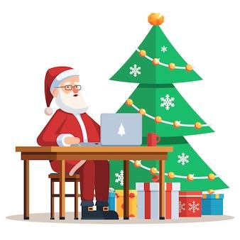 Santa claus die aan laptop werkt