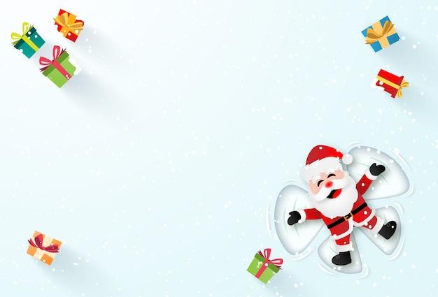 Santa claus die op de sneeuw legt en een sneeuwengel maakt