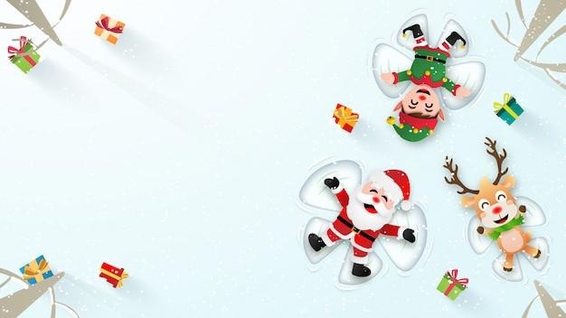 Santa claus, elf en reindeer maken een sneeuwengel