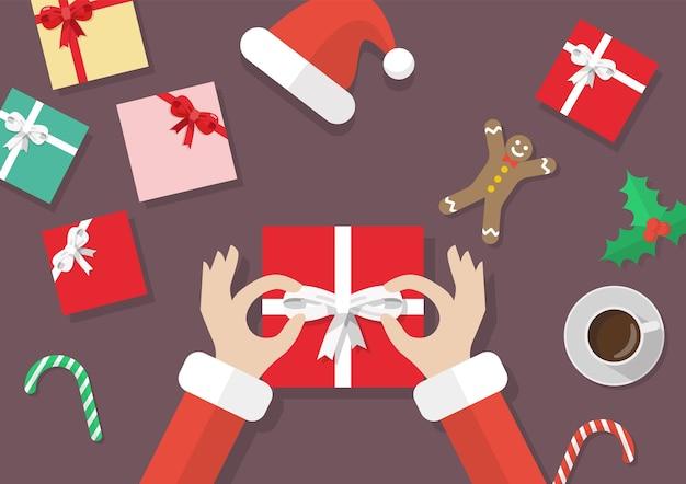 Santa hand gebonden boog op de geschenkdoos met kerst elementen