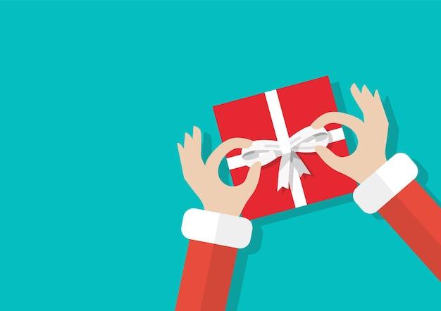 Santa hand gebonden boog op de geschenkdoos