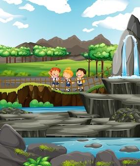 Scène met drie kinderen bij de waterval