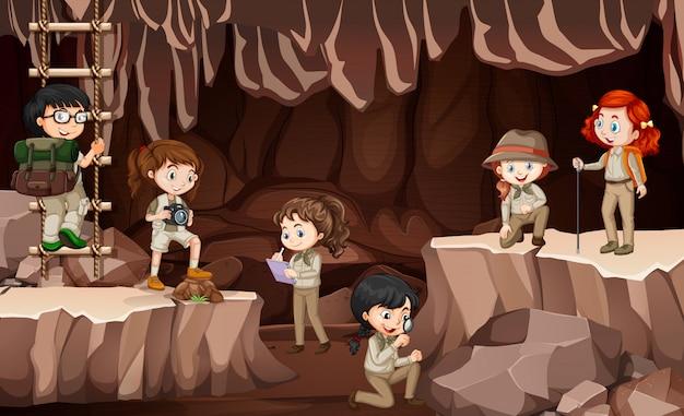 Scène met groep verkenners die de grot verkennen