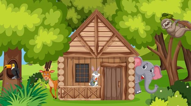 Scène met houten huis en wilde dieren in het bos