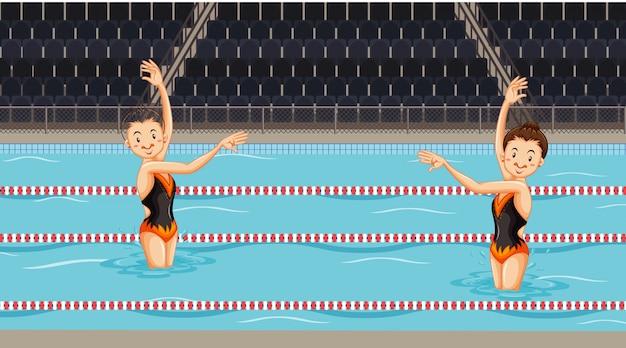 Scène met meisjes doen water gesynchroniseerde dans in het zwembad