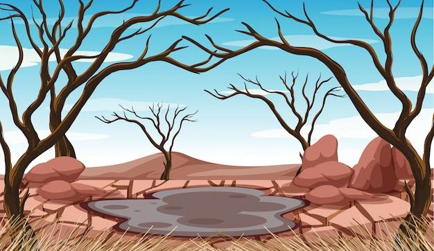 Scène met moddervijver en gedroogde bomen