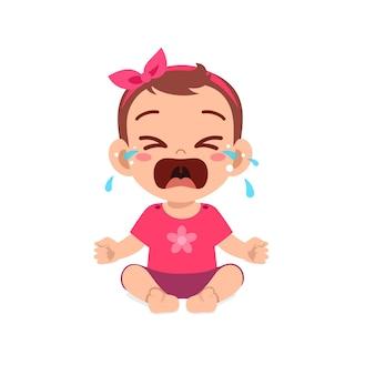 Schattig klein babymeisje toont droevige uitdrukking en huilt