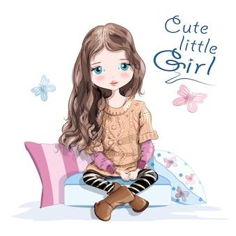 Schattig klein meisje in gebreide trui en rok zittend op zachte kussens