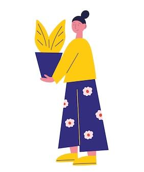 Schattig meisje draagt in gezellige kleding met in handen kamerbloemen staat in profiel plantenliefhebber