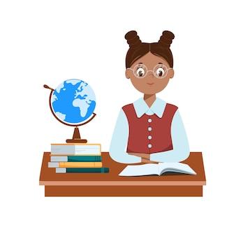 Schattig zwart schoolmeisje zit aan haar bureau