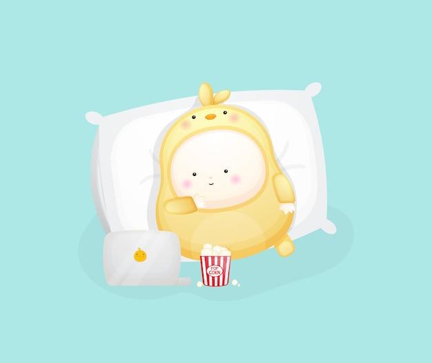Schattige baby in kuikens kostuum liegen en kijken naar film. cartoon afbeelding premium vector