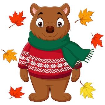 Schattige bruine beer in een trui en sjaal met herfstbladeren
