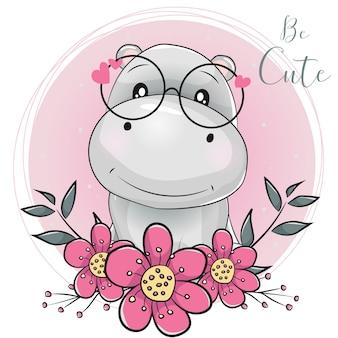 Schattige cartoon nijlpaard met bloemen met roze achtergrond