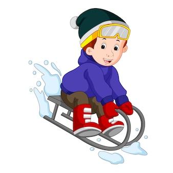 Schattige jongen rodelen in de sneeuw