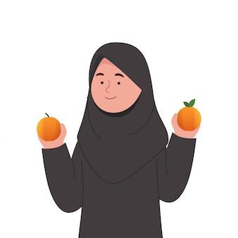 Schattige kleine hijab meisje met oranje fruit