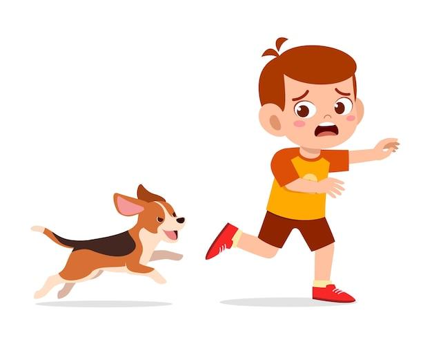 Schattige kleine jongen bang omdat hij werd achtervolgd door een slechte hond