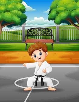 Schattige kleine jongen beoefenen van karate in de buitenlucht