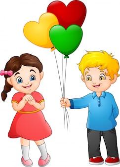 Schattige kleine jongen die een ballon geeft aan het meisje