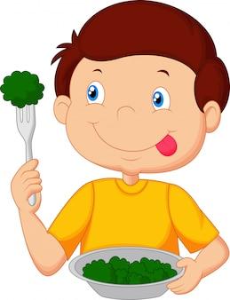 Schattige kleine jongen eet groente met behulp van de vork