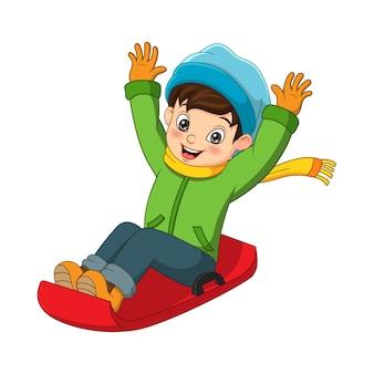 Schattige kleine jongen glijdend van de heuvel