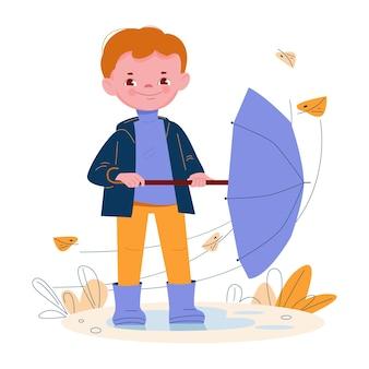 Schattige kleine jongen met paraplu in rubberen laarzen winderig weer herfstbladeren