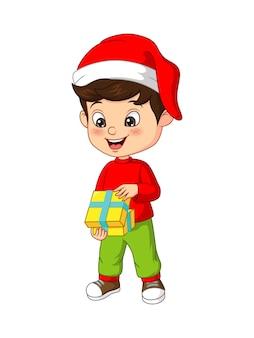 Schattige kleine jongen opent het kerstcadeau