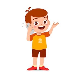 Schattige kleine jongen praten met behulp van mobiele telefoon
