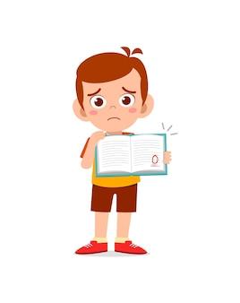 Schattige kleine jongen voelt zich verdrietig omdat hij een slecht cijfer krijgt van het examen