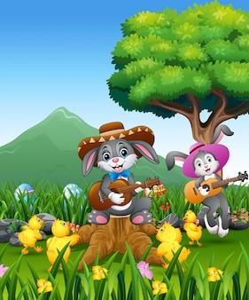 Schattige konijntjes ontspannen spelen gitaar met kuikens over de aard